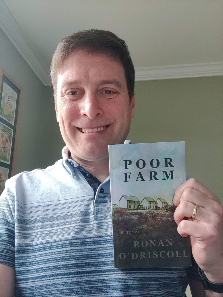 Author holding copy of Poor Farm